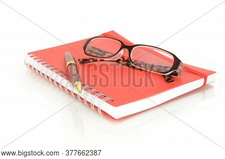 An Isolated Shot Of A Red Notebook And Pair Of Eye Glasses Over A White Background.