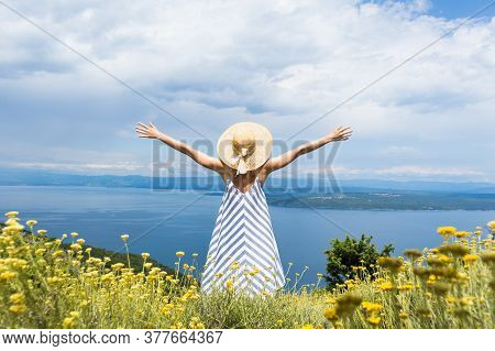 Rear View Of Joung Woman Wearing Striped Summer Dress And Straw Hat Standing In Super Bloom Of Wildf