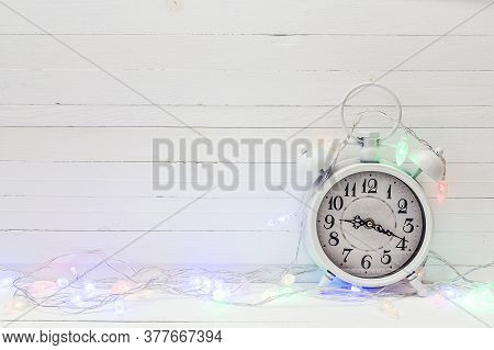 Christmas Background With Alarm Clock And Illuminated Garlands. Space For Text. Christmas Timer. Tim