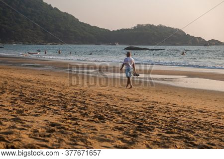 Man Walking In Waves On Beach, Goa, India
