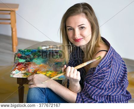 Young Beautiful Woman Artist Drawing A Picture With A Palette Of Paints In Hands