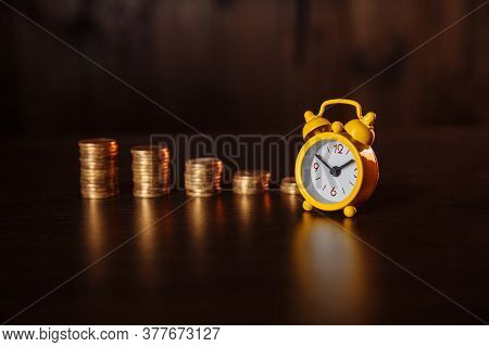 Business Financial Ideas Concept With Coins Stack And Alarmclock On Wooden Background
