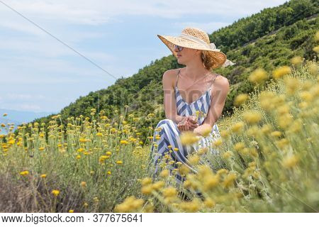 Young Woman Wearing Striped Summer Dress And Straw Hat Sitting In Super Bloom Of Wildflowers, Relaxi