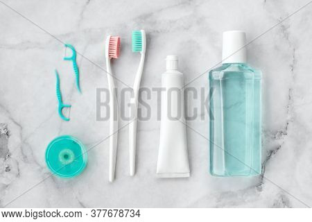 Set Of Pink And Turquoise Blue Toothbrushes, Toothpaste And Other Tools On Marble Background. Dental
