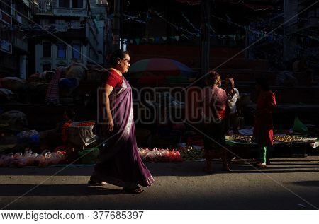 Kathmandu, Nepal - June 20, 2019: Sun shining on nepali woman in sari walking on narrow shopping street in old town, Local daily life