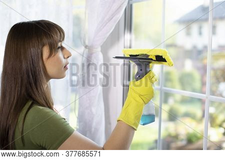 Pretty Woman In Rubber Gloves Cleaning Window Using Spray Type Cleaning Brush Window Wiper, Rubs Dus