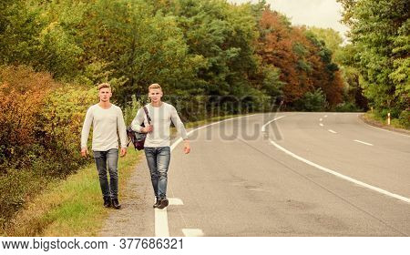 First And Foremost. Traveler Hitchhiking On Highway. On The Way Home. Future. Twins Walking Along Ro