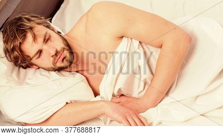 Handsome Man Yawning And Stretching His Arms Up. A Young Man Waking Up In Bed And Stretching His Arm