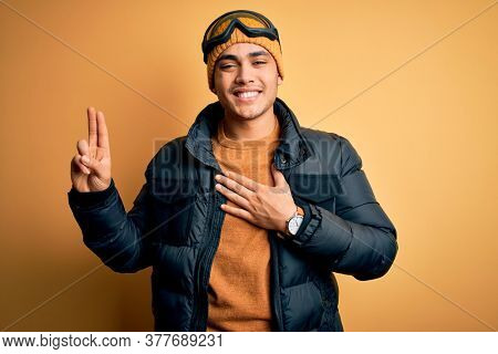 Young brazilian skier man wearing snow sportswear and ski goggles over yellow background smiling swearing with hand on chest and fingers up, making a loyalty promise oath