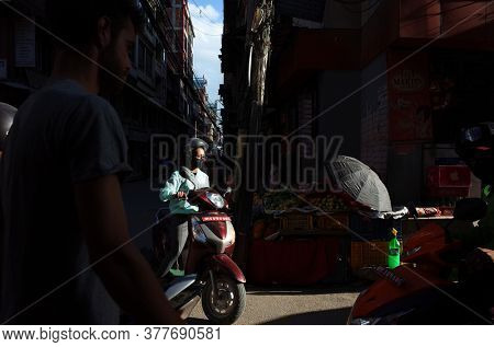 Kathmandu, Nepal - June 20, 2019: Sun is shining on young nepali woman driving scooter on narrow street in old town, Local daily life