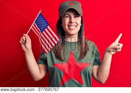 Beautiful woman wearing t-shirt with red star communist symbol holding united states flag smiling happy pointing with hand and finger to the side