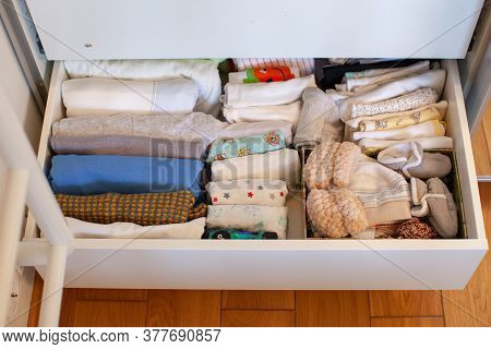 Vertical Storage Of Clothing. A Pregnant Girl Is Preparing For The Birth Of A Child. She Takes Apart