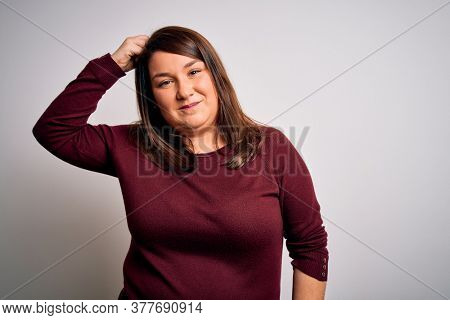 Beautiful brunette plus size woman wearing casual sweater over isolated white background confuse and wonder about question. Uncertain with doubt, thinking with hand on head. Pensive concept.