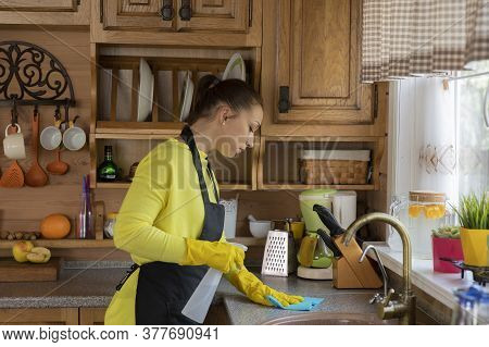 Young Beautiful Woman Housewife In Yellow Rubber Protective Gloves Cleaning House, Rubs Dust, Washin
