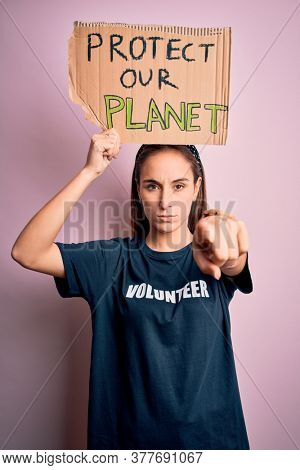Beautiful volunteer woman doing volunteering holding banner with protect planet message pointing with finger to the camera and to you, hand sign, positive and confident gesture from the front
