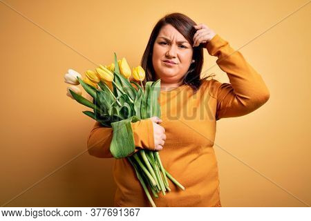 Beautiful plus size woman holding romantic bouquet of natural tulips flowers over yellow background worried and stressed about a problem with hand on forehead, nervous and anxious for crisis