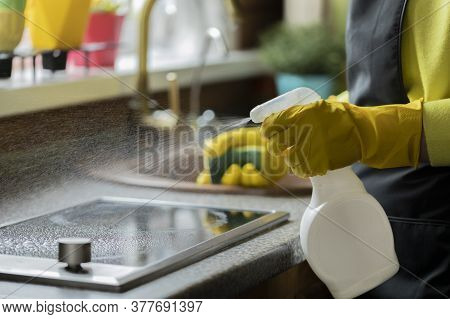 Close Up Person In Yellow Rubber Gloves Cleaning House, Wipes Kitchen Worktop Using Spray Detergent,