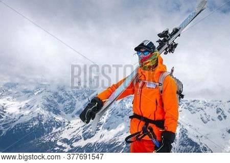 Portrait Of An Athlete Skier With Skis On His Shoulder And A Backpack On His Back. Climbing The Snow