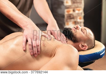 A Professional Therapist Massages The Pectoral Muscle Of An Athlete To A Man In A Professional Massa