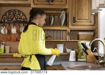 Young Cute Woman Housewife In Protective Apron Cleaning House, Rubs Dust, Washing Kitchen Worktop Us