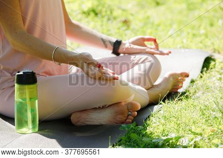 Woman practices yoga in nature. Lotus Pose, close-up
