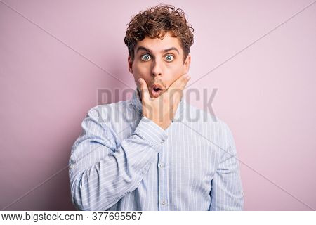 Young blond handsome man with curly hair wearing striped shirt over white background Looking fascinated with disbelief, surprise and amazed expression with hands on chin