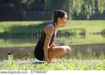 Young attractive woman practicing yoga, doing yoga balance exercise - tolasana indoor