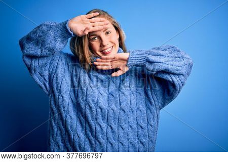 Young beautiful blonde woman wearing casual turtleneck sweater over blue background Smiling cheerful playing peek a boo with hands showing face. Surprised and exited
