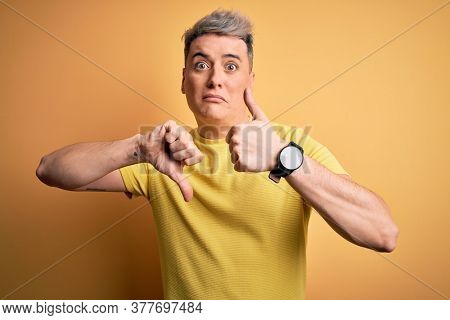 Young handsome modern man wearing yellow shirt over yellow isolated background Doing thumbs up and down, disagreement and agreement expression. Crazy conflict