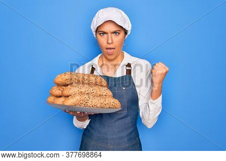 Young beautiful blonde baker woman with blue eyes holding tray with wholemeal bread cereal annoyed and frustrated shouting with anger, crazy and yelling with raised hand, anger concept