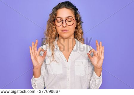 Young beautiful woman with blue eyes wearing casual shirt and glasses over purple background relax and smiling with eyes closed doing meditation gesture with fingers. Yoga concept.