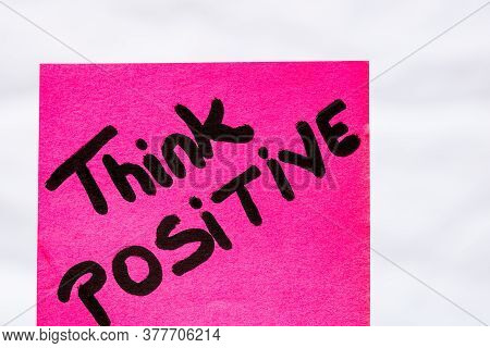 Think Positive Handwriting Text Close Up Isolated On Pink Paper With Copy Space. Writing Text On Mem