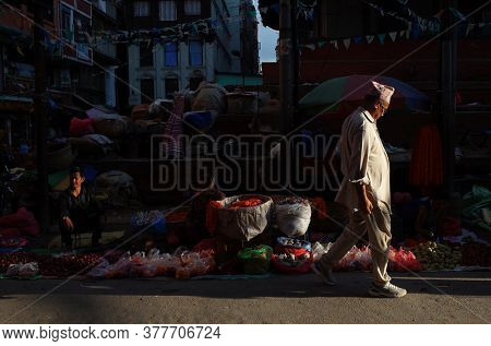 Kathmandu, Nepal - June 20, 2019: Sun shining on nepali man in traditional clothes walking on narrow shopping street in old town, Local daily life
