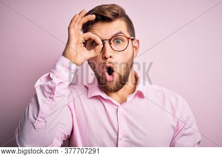 Young handsome blond man with beard and blue eyes wearing pink shirt and glasses doing ok gesture shocked with surprised face, eye looking through fingers. Unbelieving expression.