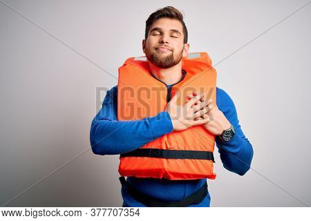 Young blond tourist man with beard and blue eyes wearing lifejacket over white background smiling with hands on chest with closed eyes and grateful gesture on face. Health concept.