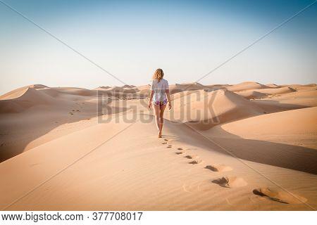 Blonde Female Caucasian Traveler Leaving Footprints In Sand Dunes When Walking In Dessert In Oman
