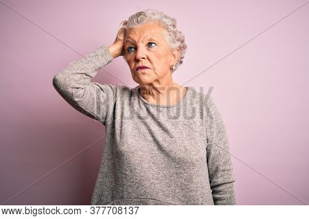 Senior beautiful woman wearing casual t-shirt standing over isolated pink background confuse and wondering about question. Uncertain with doubt, thinking with hand on head. Pensive concept.
