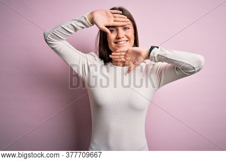 Young beautiful woman with blue eyes wearing casual white t-shirt over pink background Smiling cheerful playing peek a boo with hands showing face. Surprised and exited