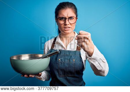 Young beautiful cooker woman with blue eyes using bowl and whisk over isolated background annoyed and frustrated shouting with anger, crazy and yelling with raised hand, anger concept