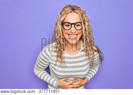 Beautiful blonde woman wearing casual striped t-shirt and glasses over purple background smiling and laughing hard out loud because funny crazy joke with hands on body.