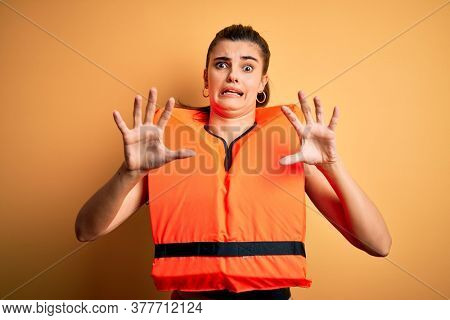 Young beautiful brunette woman wearing orange safe lifejacket over yellow background afraid and terrified with fear expression stop gesture with hands, shouting in shock. Panic concept.
