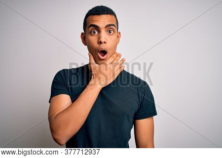 Young handsome african american man wearing casual t-shirt standing over white background Looking fascinated with disbelief, surprise and amazed expression with hands on chin