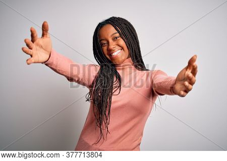 Young african american woman standing casual and cool over white isolated background looking at the camera smiling with open arms for hug. Cheerful expression embracing happiness.