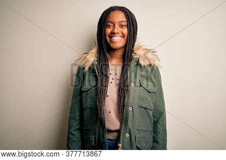 Young african american woman wearing winter parka coat over isolated background with a happy and cool smile on face. Lucky person.