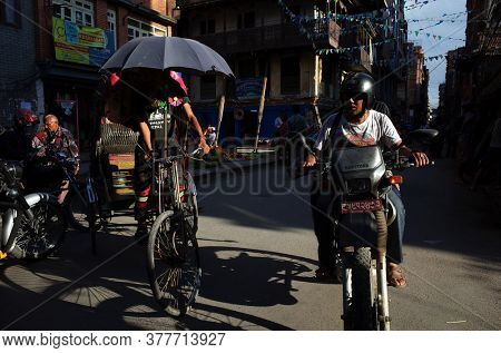 Kathmandu, Nepal - June 20, 2019: Transport traffic Man on motorbike and cycle rickshaw on narrow street in old town, Local daily life