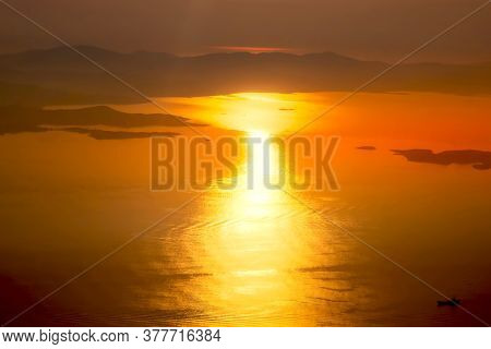 Aerial View Of Sunset Or Sunrise, Sun Over Sea, Coastline And Sea Water, Shot From Airplane