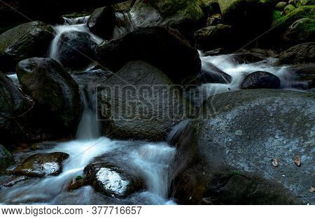 Black Rock At Waterfall With Green Moss And Sunshine On Rock. Waterfall Is Flowing In Jungle. Waterf