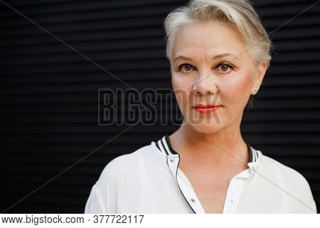 Close-up portrait of beautiful senior woman with white hair on black background.