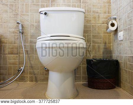 Toilet Bowl, Bidet, Rubbish Bin And Toilet Paper In The Bathroom