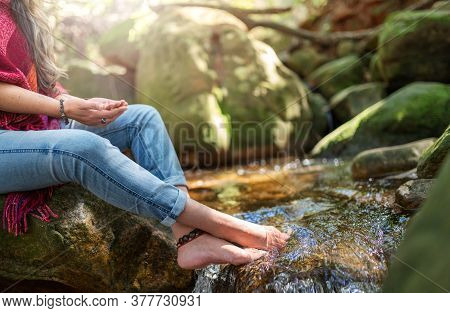 Closeup Of A Woman Meditating Alone In A Tranquil Forest With The Palms Of Her Hands Raised To The S